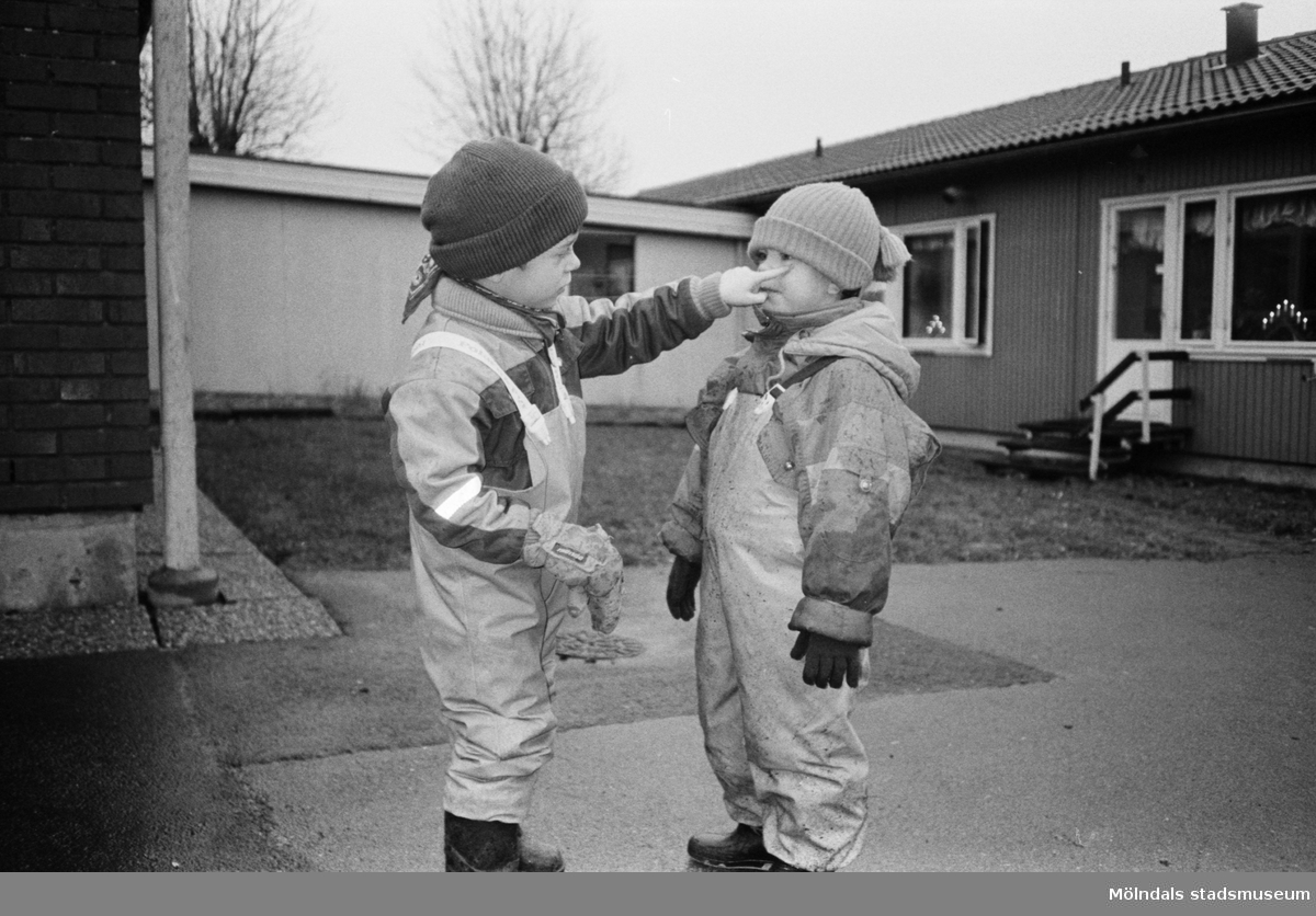 På bilden ser man två pojkar iklädda regnklädder, mössa och vantar. Den ena pojken petar den andre under ögat. De står utanför Katrinebergs daghem.