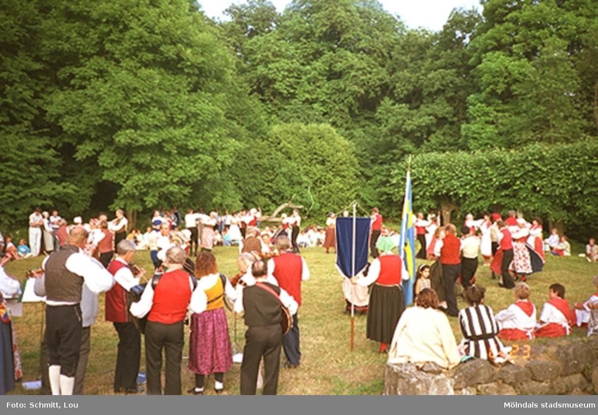Ett folkdanslag, uppklädda i dräkter, dansar inför beskådare. En kvinna står och håller en blå vimpel i ena handen och en fana, av Svenska flaggan, i andra handen. Gunnebo slottspark 1988.