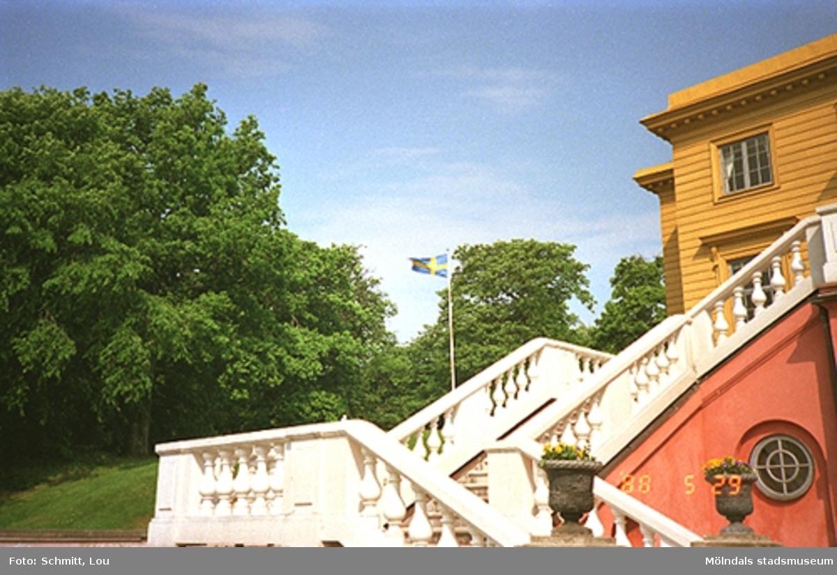 En rödokra-målad trappa med vitt räcke av sten som leder upp till Gunnebo slott. Man skymtar en liten del av slottet strax ovanför trappan. I bakgrunden ser man en flaggstång med Svenska flaggan hissad.