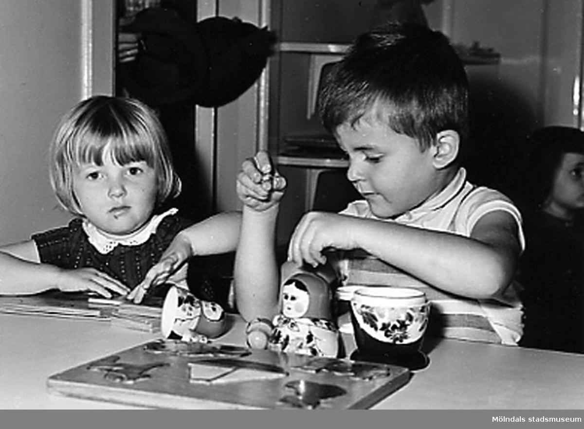 Två barn leker med en rysk docka vid Holtermanska daghemmet 1953.