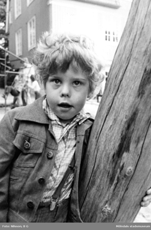 En pojke lutar sig mot en bjälke. Holtermanska daghemmet 1973.