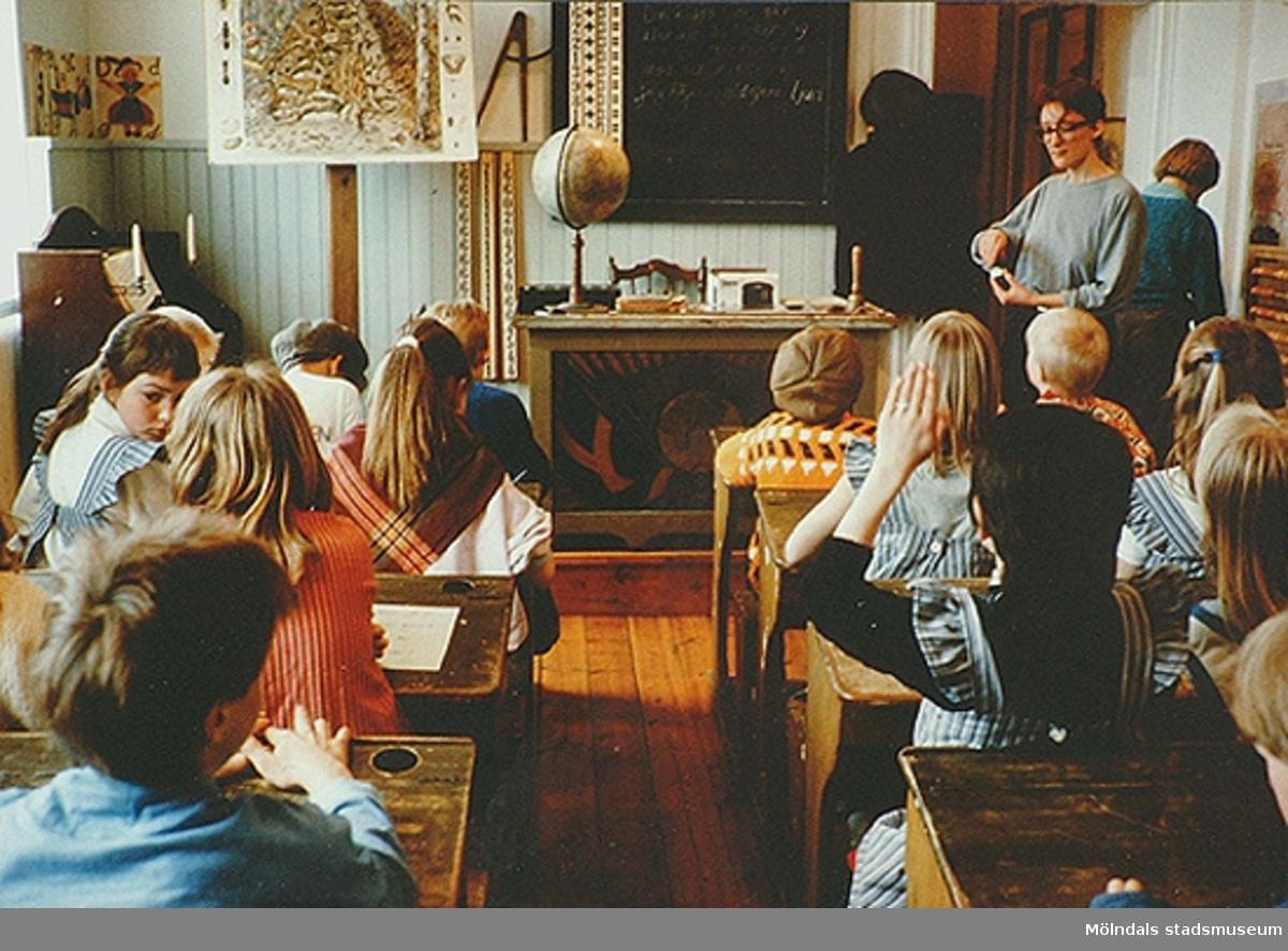 Barn som sitter i skolbänkar och skolsal av äldre modell. Mölndals museum, 1990-tal.