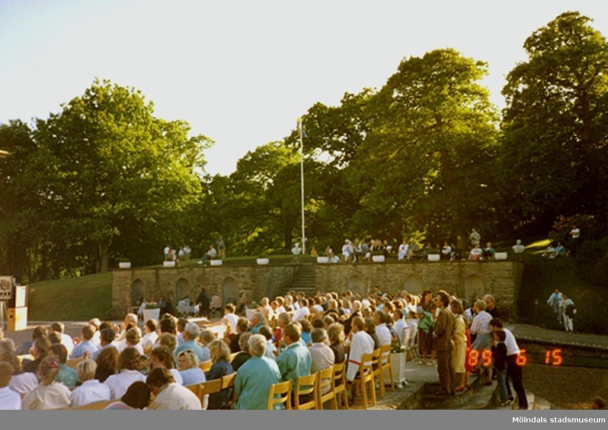 Publiken sitter i solen och har det skönt och väntar på någon form av musikevenemang.