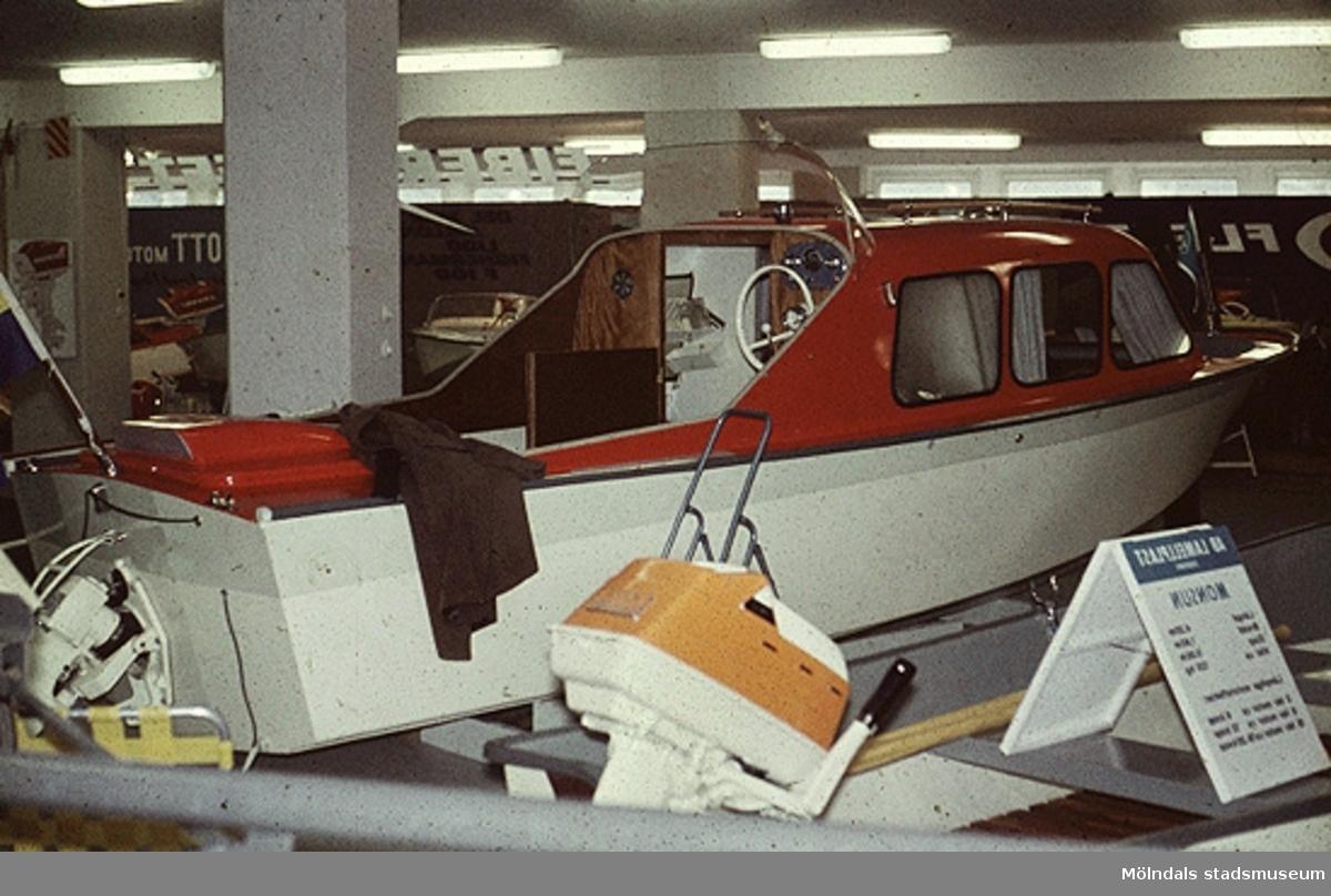 Utställning av färdig kabinbåt.Bilderna är tagna våren/sommaren 1960, ungefär där nu Almåsskolans slöjdsal är belägen i Lindome. Fabriken ägdes tidigare av Colldens möbler. Fabrikslokalerna ägdes sedan av Hj.C. Samuelsons AB, som tillverkade i huvudsak butiksinredningar till  Åhlen & Holms varuhus. Vid årsskiftet 1959-1960 flyttade Samuelson tillverkningen till Floda. Fabriken övertogs av AB Lamellplast, ett företag inom Persöner koncernen, Ystad. AB Lamellplast  tillverkade båtar och en husvagnstyp av glafiberarmerad  polyesterplast. Plastmassan levererades av SOAB Mölndal.