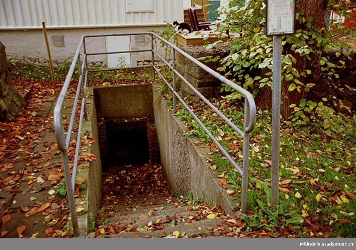 """Ingången till det som en gång var syratornet """"Sodom"""", år 2001. På 1870-talet byggdes syratornet """"Sodom"""" strax intill Royens gata och innanför Franckegatan. Där tillverkades svavelsyrlighet som leddes i blyrör ner till Stora Götafors. Där framställdes pappersmassa enligt sulfitmetoden. I Rosendahls fabriker (pappersbruket) gjordes sedan papper. Syrligheten var starkt frätande. Blyrören lades därför i en kulvert med tegelvalv och nedgångshål, så att rören lättare skulle kunna ses över. """"Sodoms torn"""" är rivet och kulverten har inte varit i bruk sedan dess. För att man ska kunna se in i kulverten gjorde Gatukontorets parkavdelning 1992 i ordning kulverten och dess trappa."""