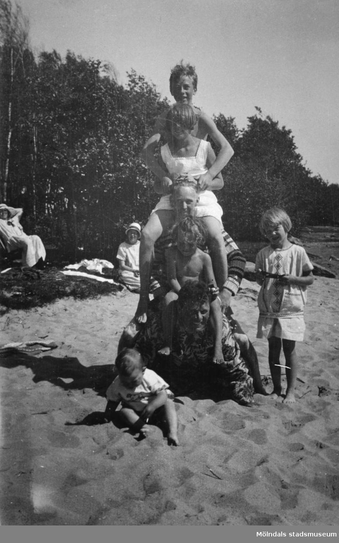 Vuxna och barn idrottar på stranden vid Tulebosjön, cirka 1930.