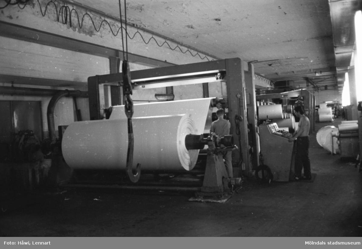 Män i arbete vid maskin. Rullmaskin 5, byggnad 10. Papyrus, hösten 1970.