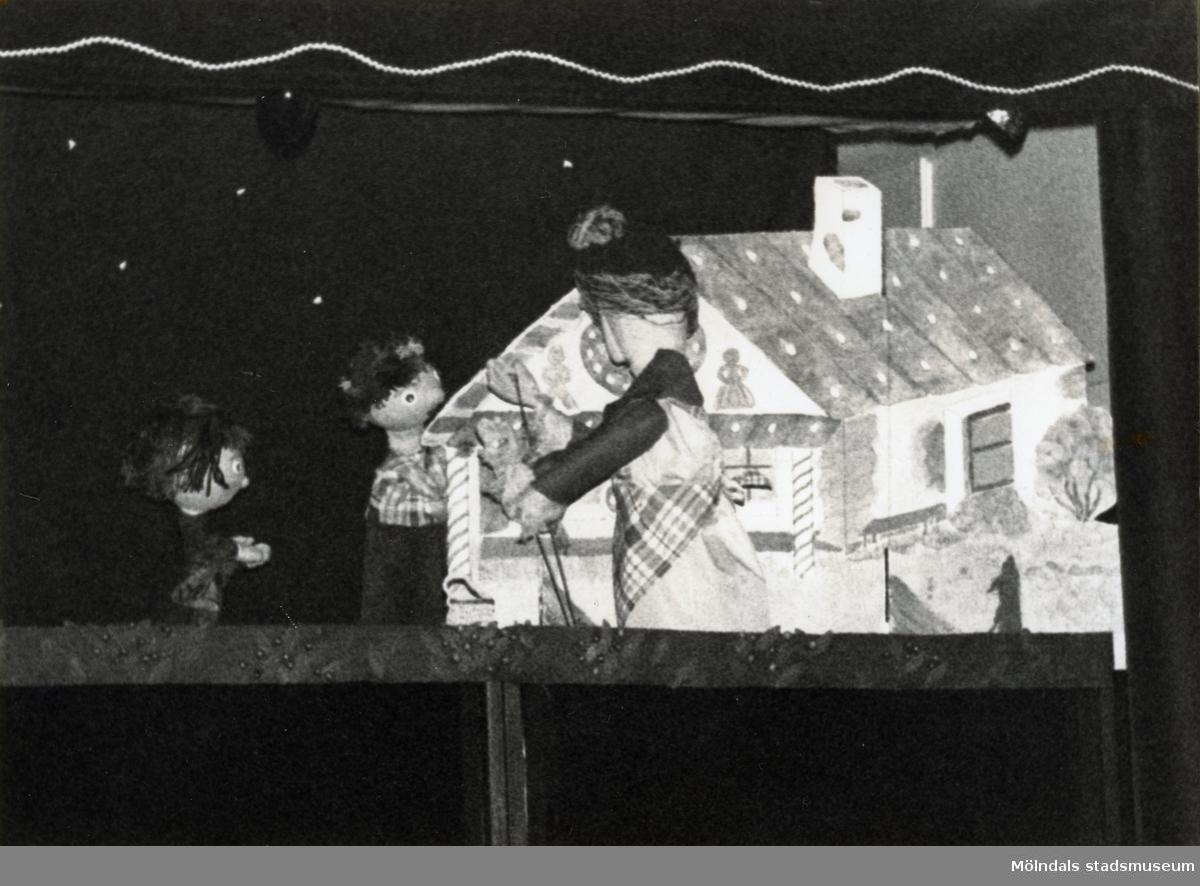 """Föreställning av """"Sagan om pepparkakshuset"""" i september 1980. Fotografi ur album tillhörande Blanka Kaplan.  Sagan om pepparkakshuset är en bearbetning Blanka Kaplan gjort av den klassiska sagan om Hans och Greta som lämnas åt sina öden ute i skogen. De stöter på ett pepparkakshus och en häxa som tillfångatar dem i syfte att göda upp och äta Hans, och nyttja Greta som tjänare. Barnen överlistar häxan och kommer hem igen med häxans skatter. Sagan gick som dockföreställning under våren och hösten 1980 i TBV-husets lokal på Hagåkersgatan 4 i Mölndal."""