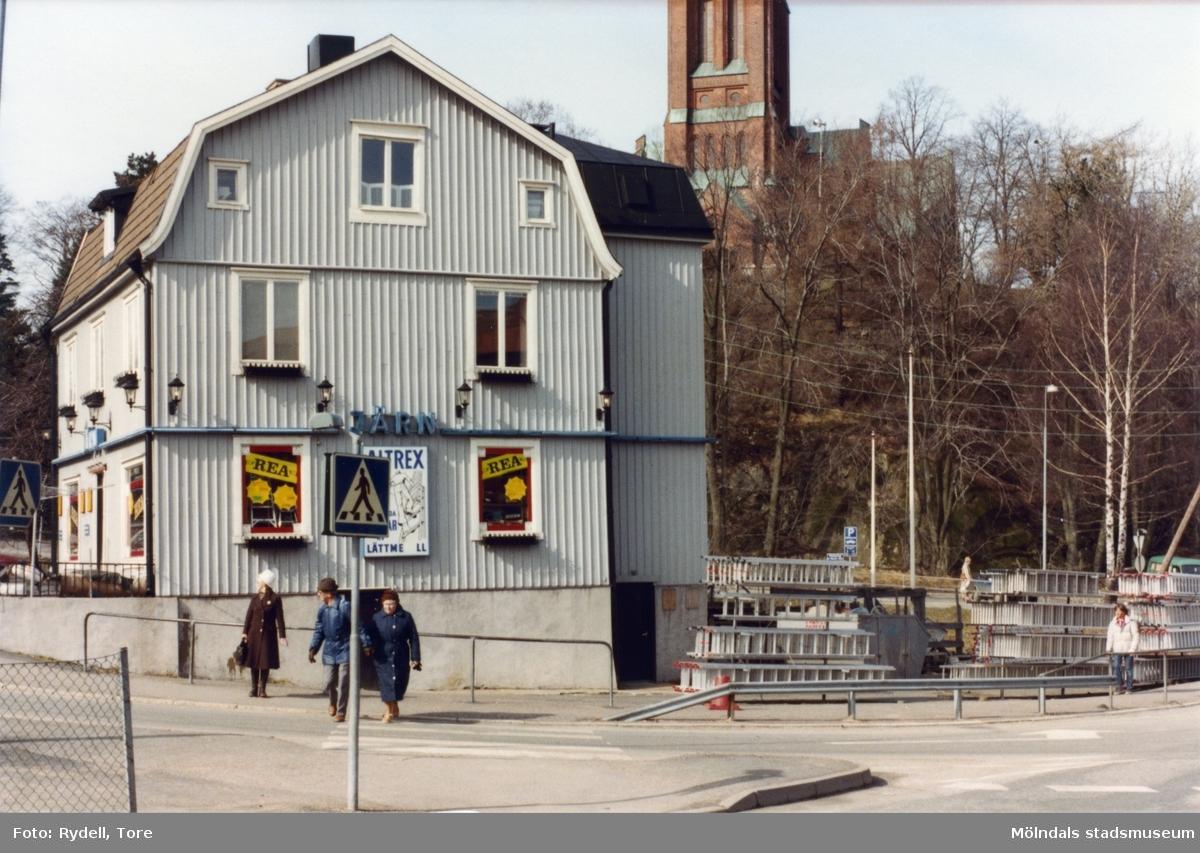 Joel Jacobsons järnhandel vid Frölundagatan. I bakgrunden ses Fässbergs kyrka.Fotografi ur album som tillhört Christina Rydell. Bilderna i albumen är delvis från Papyrus där Christinas far Tore Rydell arbetade, men också från Kvarnbyn, Ryet och folkliv i Mölndal. Tore tog ofta med sig kameran till Papyrus där han fotograferade sina arbetskamrater i arbete, men också fester och föreningsliv.