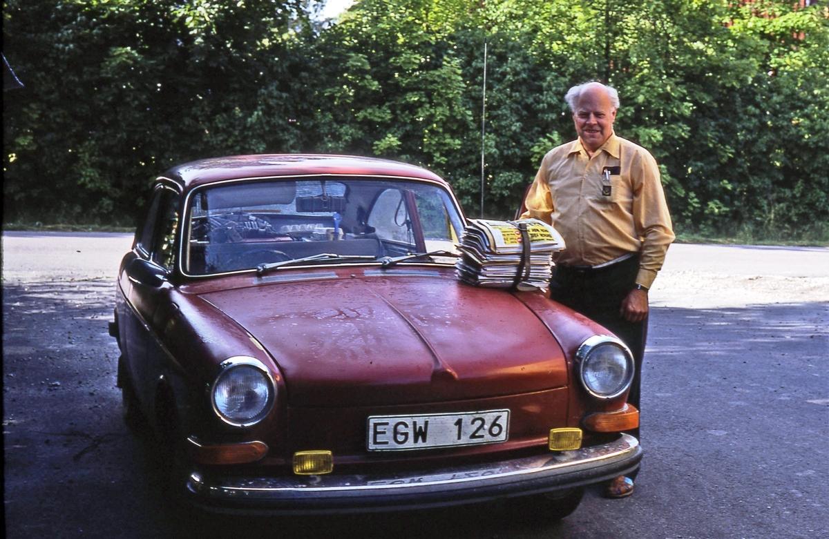Gunnar Jansson står vid en röd bil. En bunt tidningar ligger på motorhuven. Vid brevbärarexpeditionen Olsborgsvägen i Vallentuna.