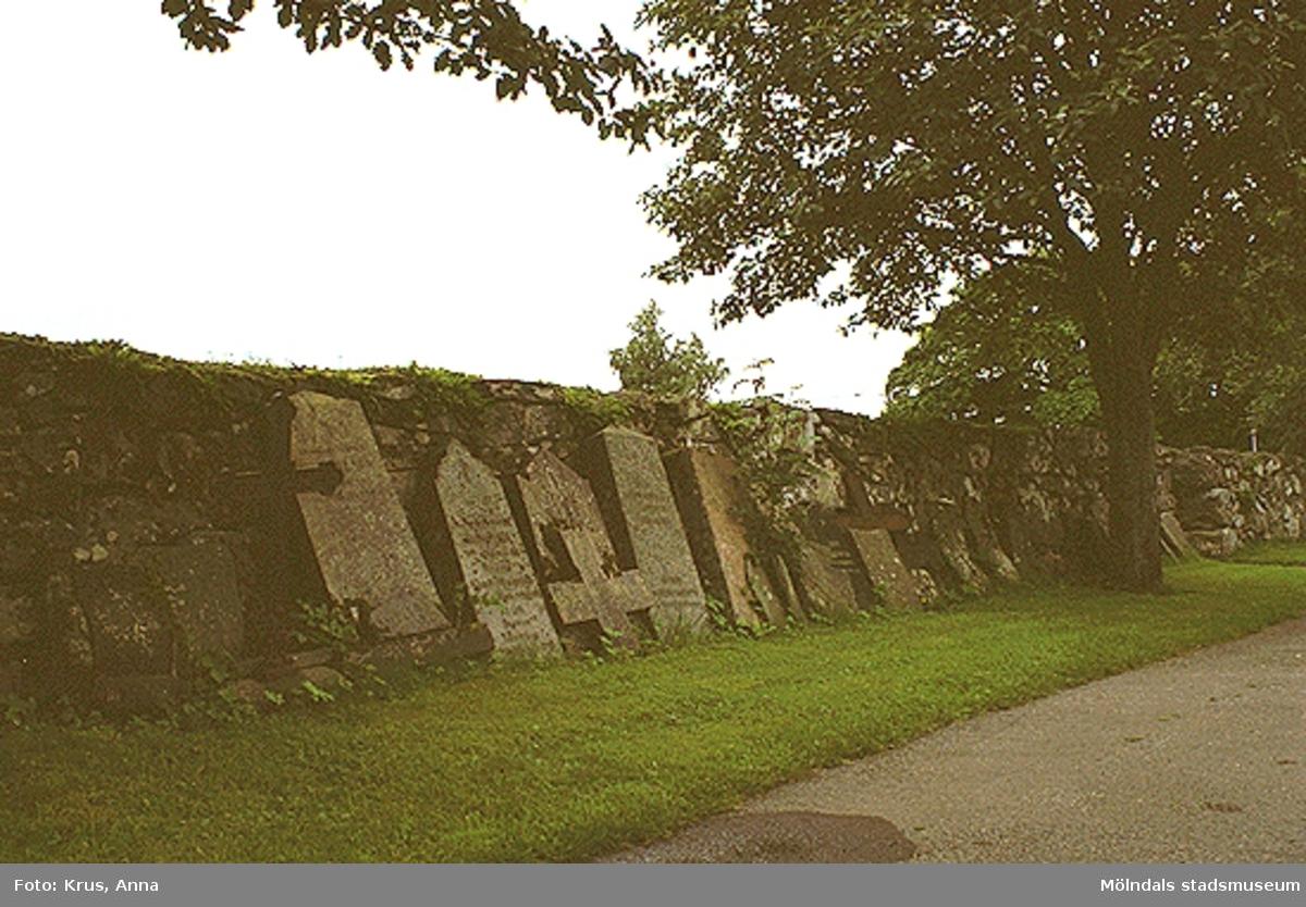 Lindome 11:1. Gamla gravstenar längs kyrkogårdsmuren.