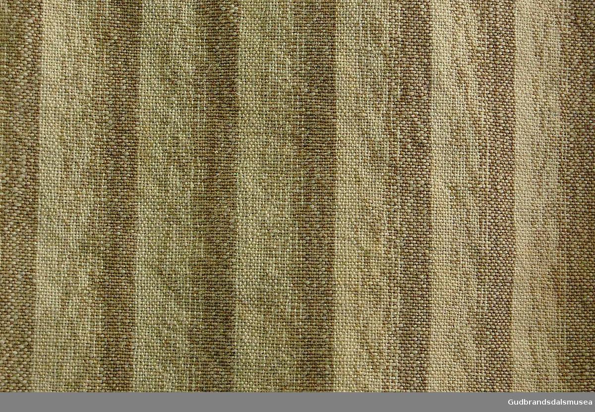 Stakk i tykkere, vevd stoff. Striper i brunt, beige/hvitt. Påsydd to svarte bånd rundt langs nedre kant, påsydd grønn kant helt nederst. Med splitt. Sydd inn en liten bit i stripete lyseblått, beige og grønt over innsydde folder bak i liv, en hekte sitter igjen i liv, ellers løse tråder og søm der stakken festes rundt.