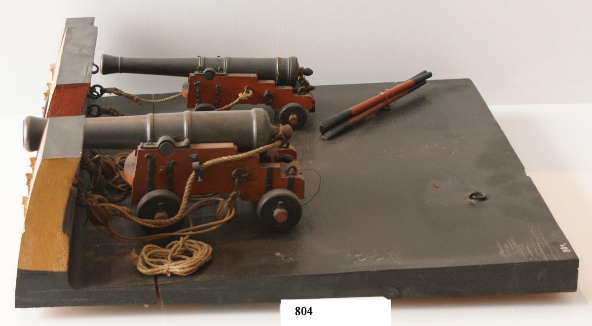 Kanonmodell: 24-pundig styckelåda av engelsk modell, med kanon. Modell av trä. Lavetten rödmålad, kanonen svart. Tillbehör: 1 st brok, 1 st riktkil, 2 st spakar och 2 st taljor. Lavetten L = 510 mm B = 480 H = 140 mm.