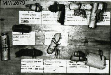 Patron till kammarladdningsgevär m/1851. Två stycken (utan laddning) uppsatta på samma platta som ovanstående (MM 2678)