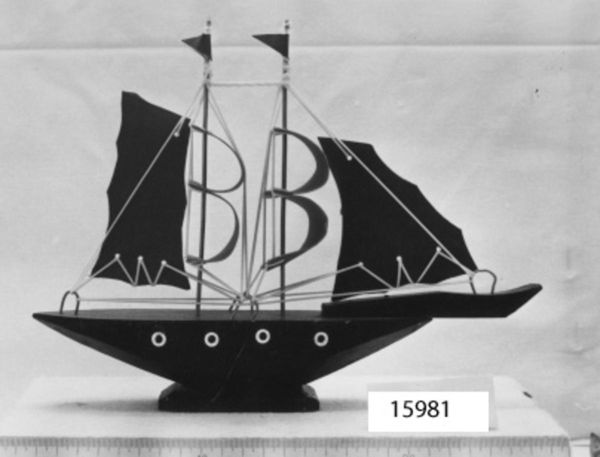 Modell av tvåmastat segelfartyg (fantasi). riggad och satt med röda segel, typ en brigg. Riggningen av gul plasttråd. Skrovet massivt likformat med spetsiga ändar, svartmålat. På dess sidor 4 vita öljetter (hyttfönster). Skrovet fast på låg fot.