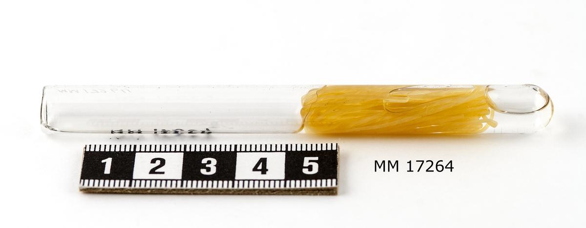 Gul tråd cirka en meter, ligger i vätska i ett tillslutet glasrör.
