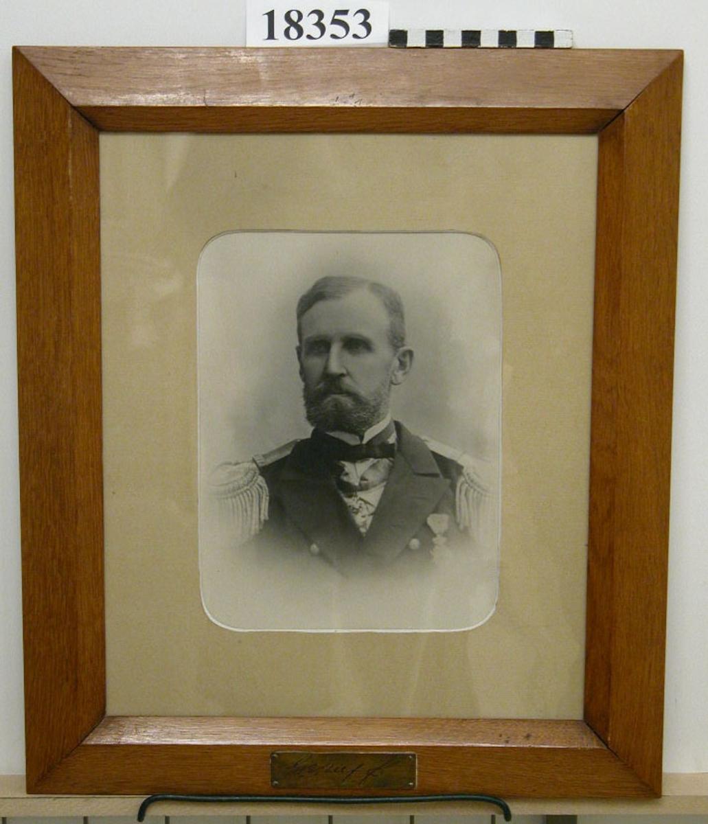 """Fotografi inom glas och ram föreställande G.E. Ulff. Bröstbild av man klädd i paraduniform med medaljer och epåletter. Välansat skägg. Passepartout  B = ca 50 mm. Ram av ljus ek fernissad, profilerad. Nederst mässingsbricka med graverat namn efter namnteckning: """" G.E. Ulff """". Baksida kartong försedd med lapp: """"Gustaf Emanuel Ulff  född 1833 5/3 död 1912 11/12"""". Neg.nr A 376 6:14"""