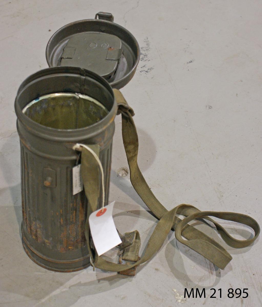 """Behållare till gasmask tysk modell. Tom plåtbehållare. Enligt uppgift: Upphittad på Västkusten under andra världskriget. Bestående av ansiktsskydd och filterbehållare. Masken förvaras i en plåtask. Ansiktsskyddet är märkt med """"Bibkler FPU 12377"""". SSS 82"""