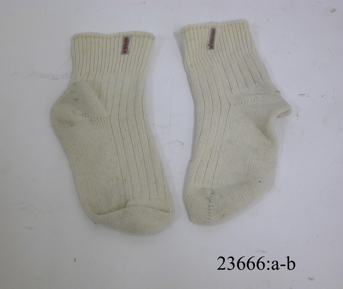 Benvita ribbstickade ankellånga strumpor. Stickning i skaft och fot, tre räta och en avig maska. Stickning i mudd en rät och en avig maska. På utsidan av muddarna en påsydd textillapp med text i rött: MARINEN.
