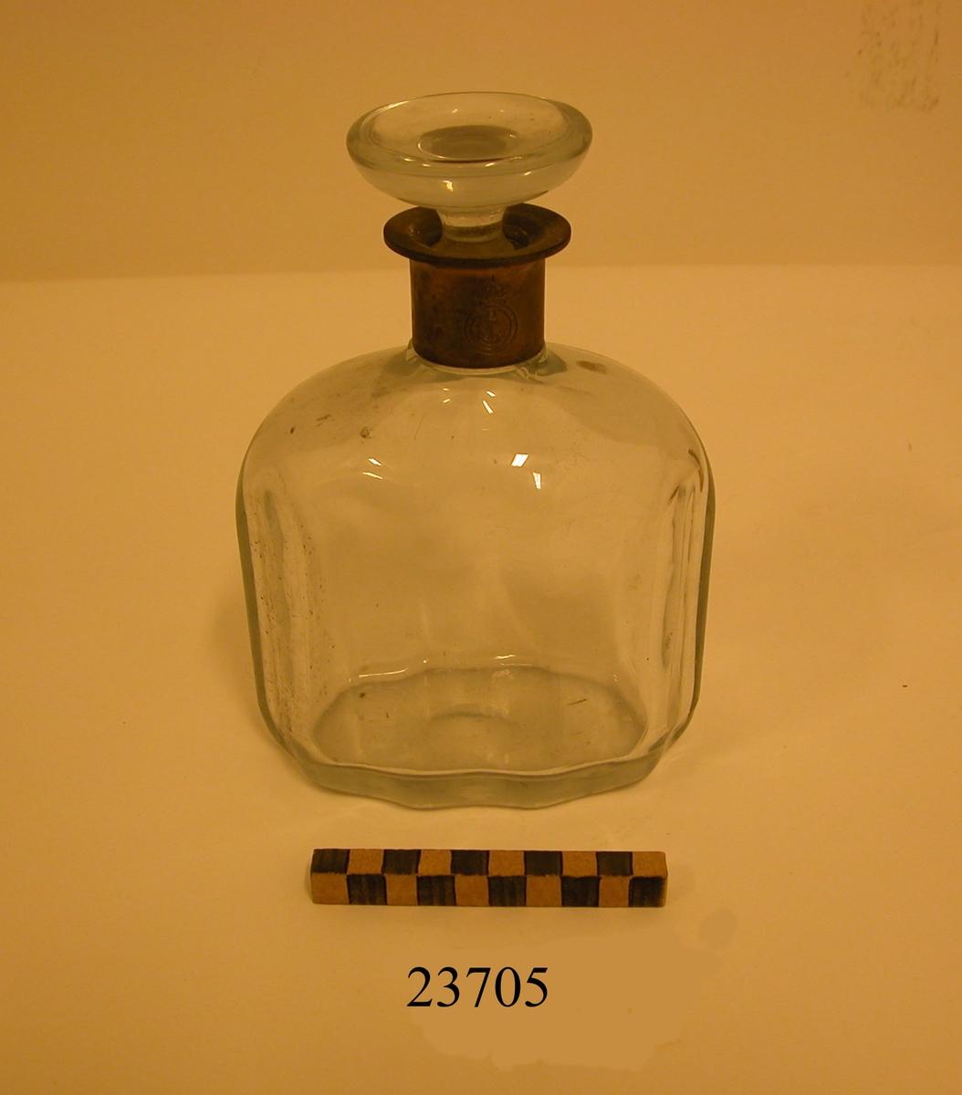 Karaff och propp av glas. Halsen försedd med krage av silver med ingraverat emblem, ankare med tross omgivet av cirkel och krönt med krona. Sjövärnskåren. Samt stämplad med kattfot och R8 (1943). Karaffen har rak oval form. Livet något vågformat.