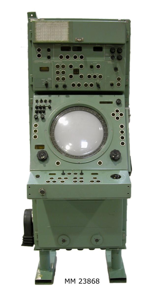 """Centralinstrument till torpedcentralinstrument (TCI) 200/S. Nr: 207838. Turkos- eller grönlackerat, rektangulärt instrument av metall. På undersidan sitter två ben. På ovansidan sitter två beslag för montering av instrumentet. Överst sitter en lucka varunder det sitter säkringar samt manövervred och visare för kraft- och räknekontroll. Där sitter en visare för drifttiden: 4046 timmar och 9 tiondelar. På luckans utsida sitter ett """"Anvisningsblad för radarnavigeringsskivställ typ 4"""", fastklistrat med tejp. Nedanför luckan finns en mängd manövervred, bland annat visare för avläsning av fart/avstånd, kurs/bäring och målvinkel. Torpedräknare, torpeddata, bäringsdragning/skillnadsvinkel och radar. Nedanför sitter en översiktsindikator tillsammans med manövervred."""