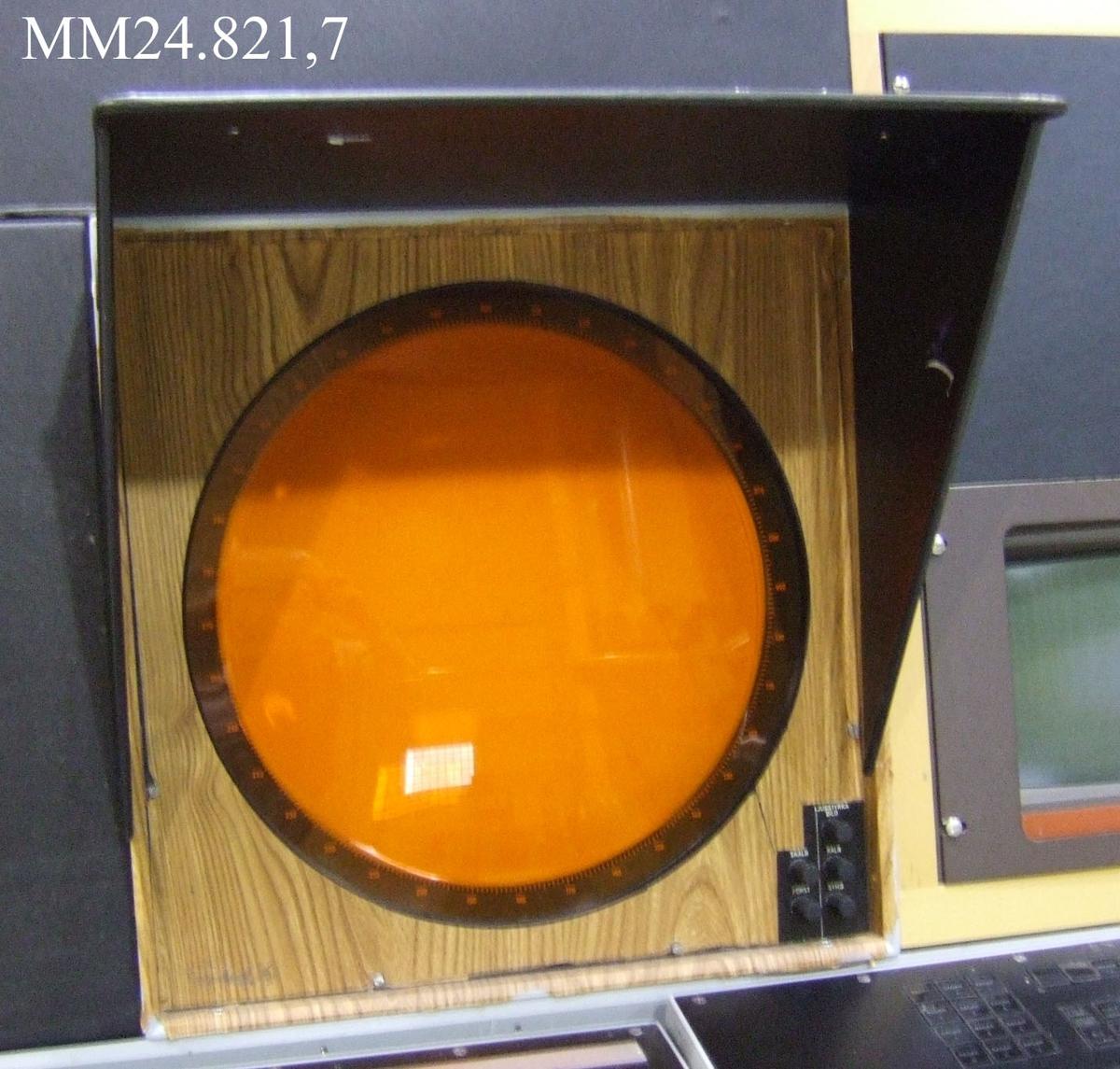 Fyrkantigt svart med rund orange skärm i mitten. Nere till höger skruvknappar för att justera bild med mera. På djupet är planpolärindikatorn grå och längst bak sitter ett flertal uttag för sladdar och kablar.