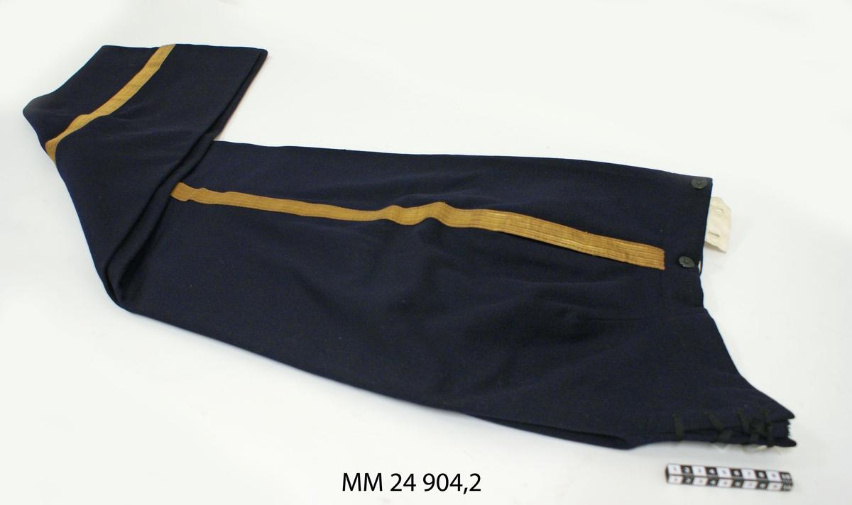 """Byxa av mörkblått  kläde/ylletyg, försedd med 30 mm bred guldgalon på vardera yttersömmen. Gylf med fyra svarta knappar samt snörning i linningen baktill. I linningen fodrad med vitt bomullstyg. På vänster insida försedd med märklapp med texten """"Molin & Möcklin Stockholm"""" samt tillskrivet på skrivmaskin: """"Jan 1940, Löjtnant Stig Örtendahl""""."""