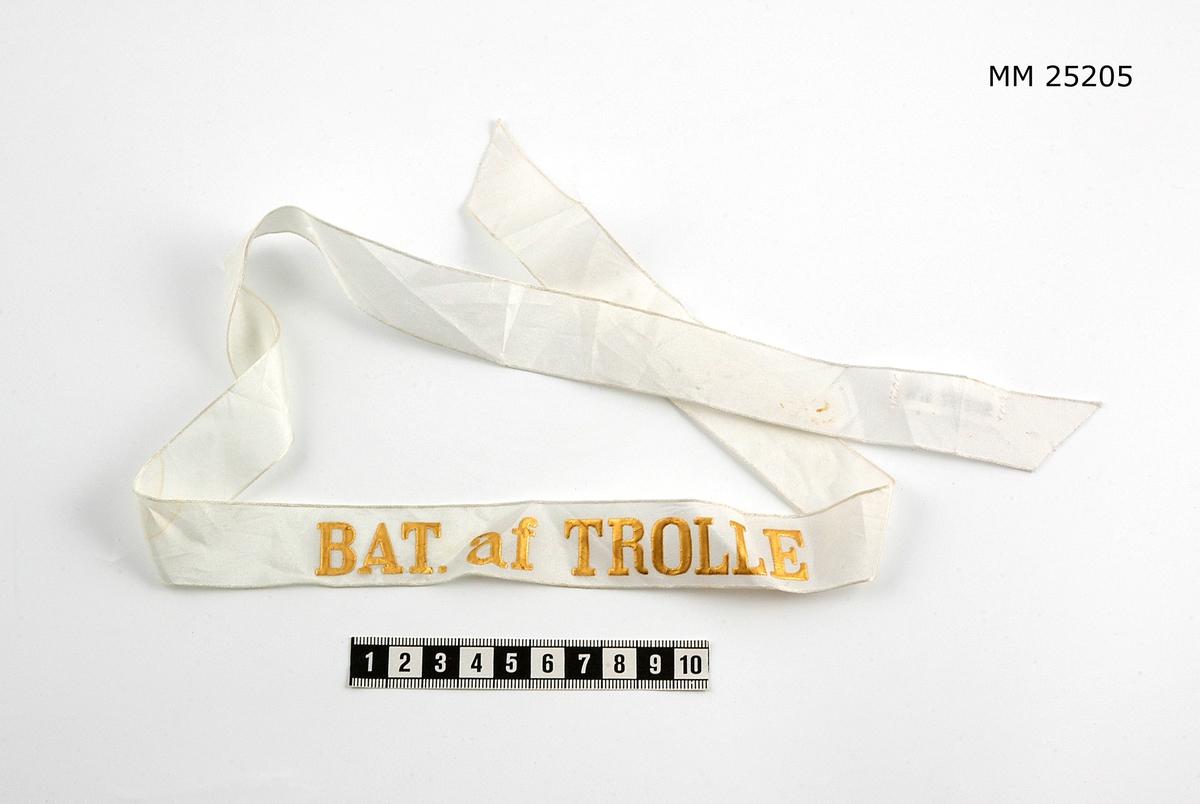"""Mössband av sidenrips. Vit med text i guld: """"Bat. af Trolle""""."""