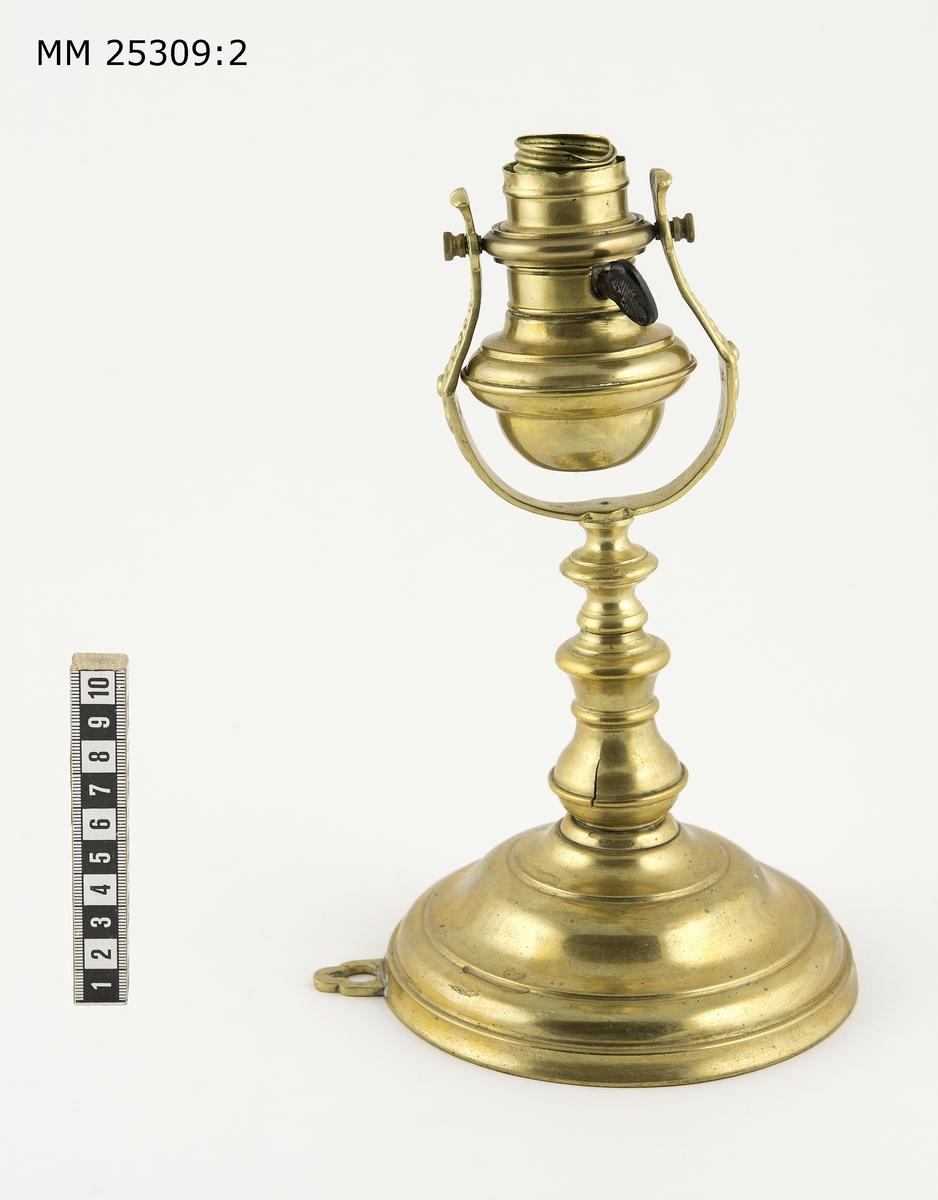 Skeppslampa av mässing med elinstallation. Vägghängd lampa bestående av rund väggplatta med upphängningsögla. Svarvad lamparm med kardanupphängt lamphus. Armarna som håller lamphuset är ornamenterade. Elinstallation i lamphuset samt svart tändknapp av bakelit. Lampglas saknas.