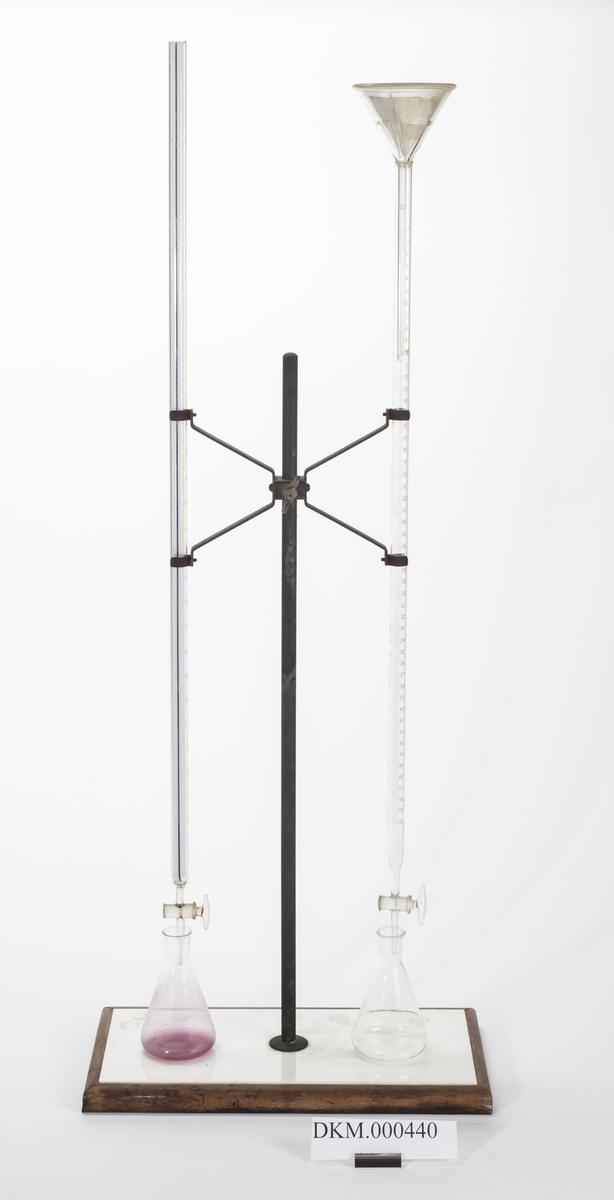 Stativet består av en rett stang og en holder med fire armer som er skrudd fast på stanga. Holderen har fire armer og på hver side av stanga er det ett reagensrør som holdes oppe av av to slike armer. Det ene røret er noe lengre enn det andre. Stanga er montert på en plate.