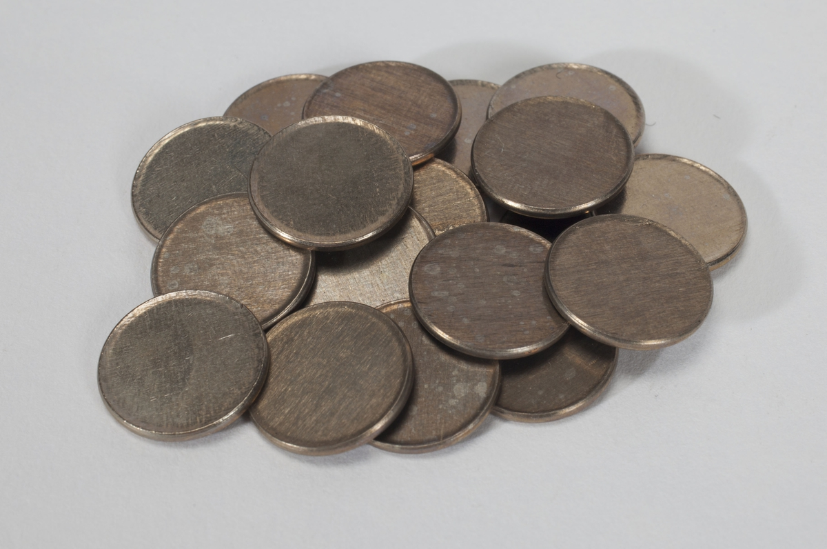 19 runde metallplater med opphøyd kant.
