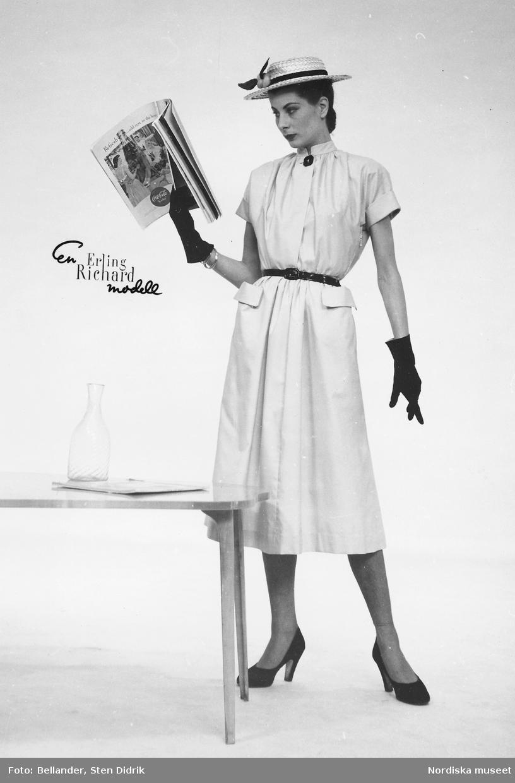 Modell i klänning med skärp, stråhatt, pumps och handskar, tidning i handen. Från Erling Richard.