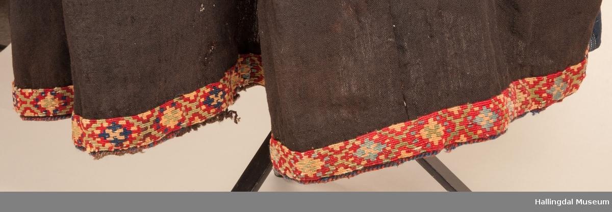 Kone fra Nedre Hallingdal i arbeidsklær.  Drakten er sammensatt av mange ulike draktplagg på Hallingdal Museum.  Stakk HFN 08404, Forkle HFN 08405, strieforkle, grønn trøye, skaut, lue og belte.  Kona står utstilt i den faste bunadutstillingen på Hallingdal Museum, Nesbyen.  Hun viser hvordan konene kledde seg når de arbeidet.