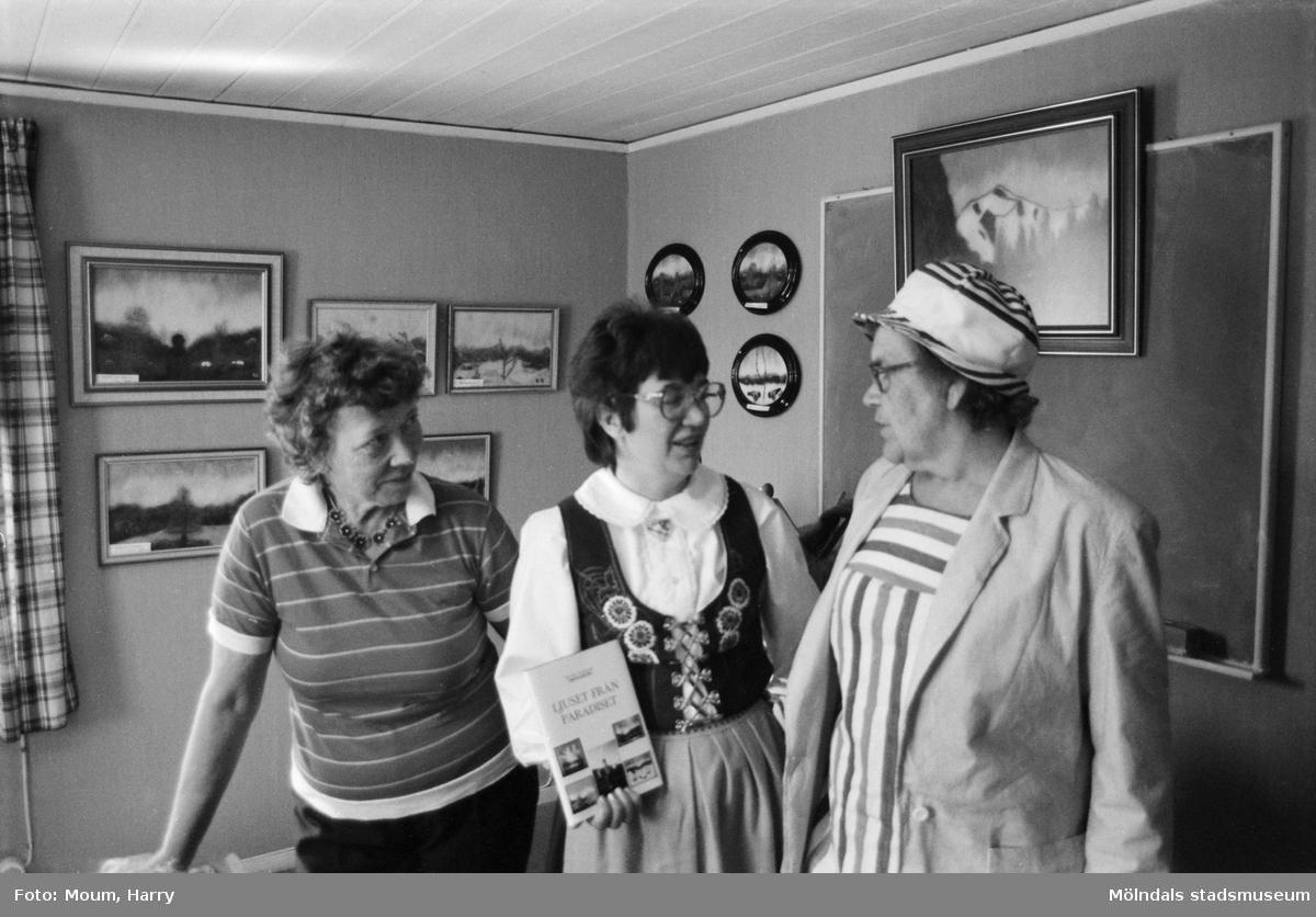 Kerstin Söderlund ställer ut i ABF-stugan i Lindome, år 1984. Här tillsammans med två andra damer. I bakgrunden hennes tavlor.  För mer information om bilden se under tilläggsinformation.