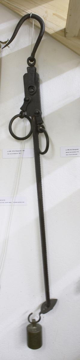 Kan veie et skippund (160 kg). Loddet er merket med en M. Stor krok øverst, deretter et jernstykke med to store ringer, en på hver side. En lang stang går herfra og har visse merker fra topp til bunn (målemerker) nederst en krok som loddet henger i.
