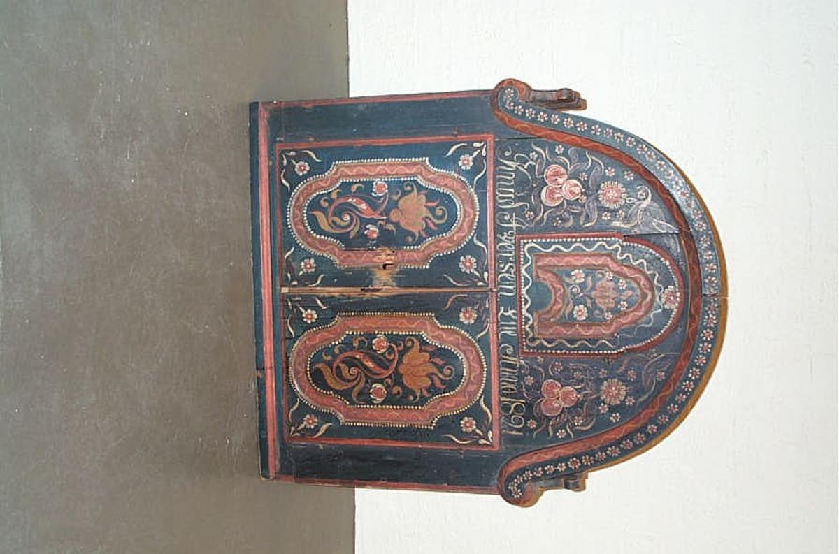 1 vægskap.  Et vægskap 74,5 cm bredt, 87,4 cm høit med avrundet overdel. Skapet er delt i 2 avdelinger. Det nedre har 4 rum med to døre foran, det øvre har et rum med rundbuet dør, der med trælaas laases fra underste rum. Forsiden vakkert rosemalt. Over de doble døre staar følgende inskription: Knud  Iversn.Lue Anno 1821. Kjøpt av Ole Iversen Bø, Lærdal.