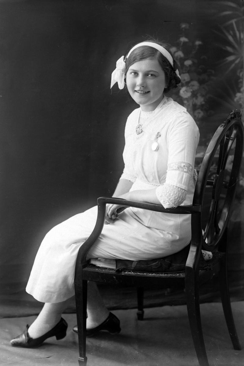 Studioportrett av ung kvinne i stol.