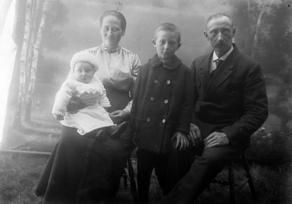 Studioportrett av et eldre par med en gutt og et spedbarn.