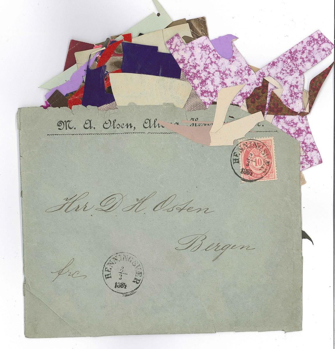 Ein brukt brevkonvolutt som inneheld mange små avklypp av papir og blonder. Papirbitane er i mange ulike fargar og mønster.