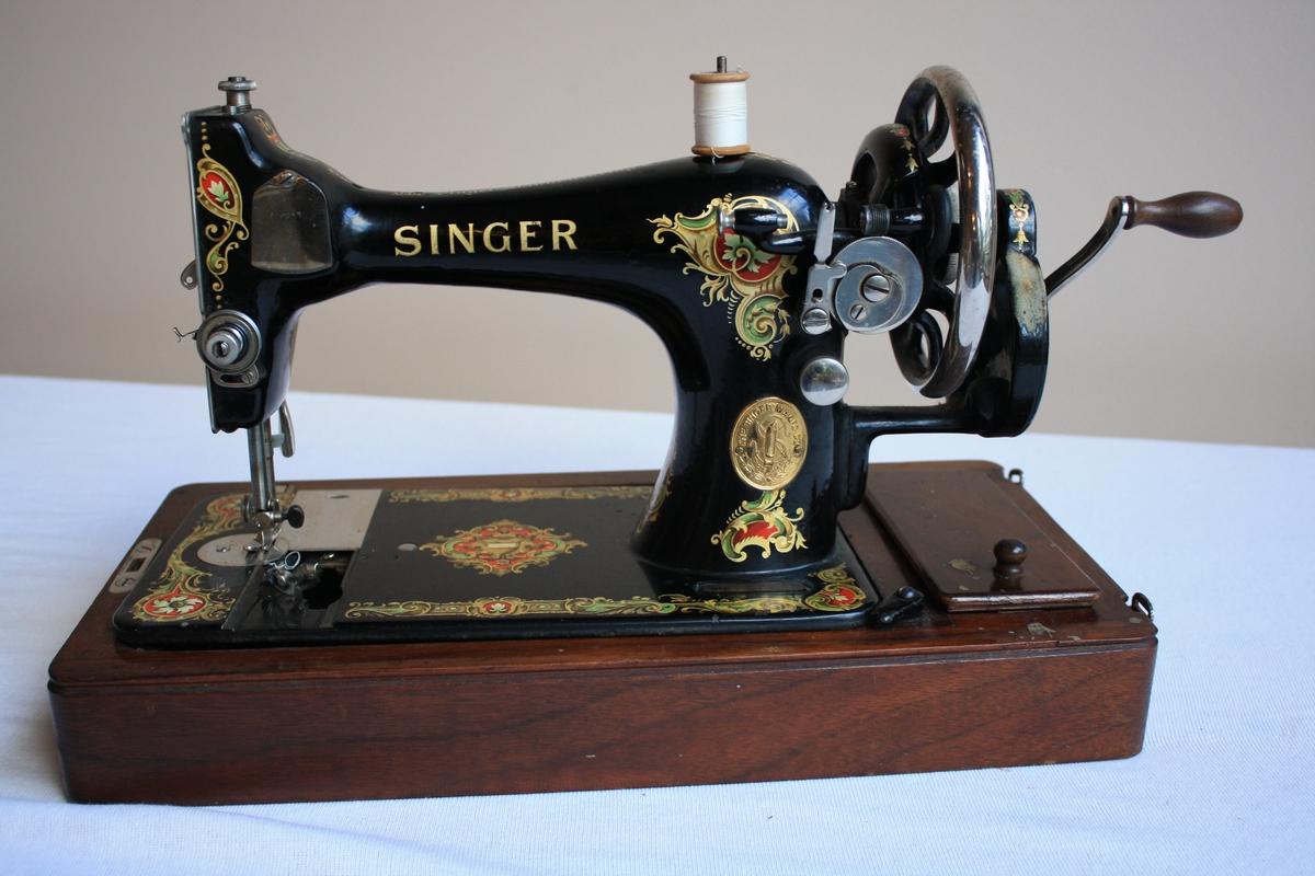 Symaskin med handsveiv på tresokkel. Verktøyskrin intregrert i tresokkelen. Heile maskina er dekorert  med blomster og div. mønster i raudt, grønt og gult.