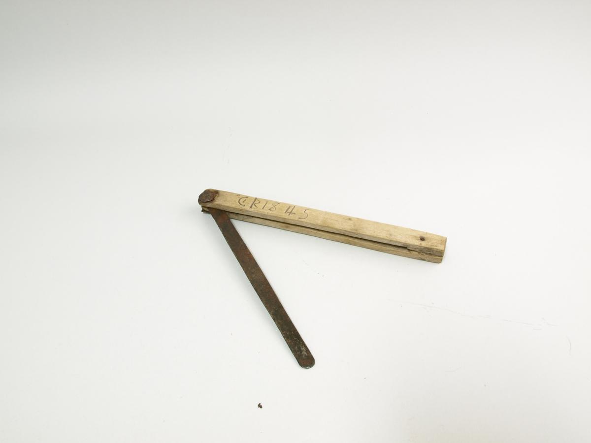 Lausvinkel av tre med vinkelblad i metall (smidd). Vinkelbladet er klinka ved ledd for regulering. Tredelen har vore i eit stykkje men brot på ende gjer at vinkelen her er halde saman med ein jarnstift. Bruk: Regulerbar vinkel.