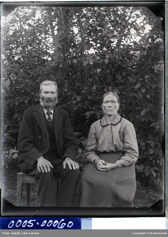 Portrett av eldre mann og kvinne i helfigur i dress og bluse med skjørt.
