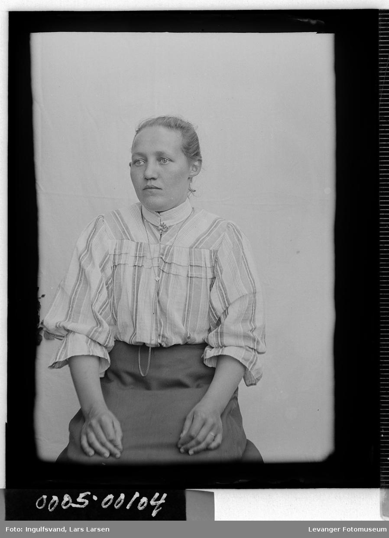 Portrett av kvinne i halvfigur iført bluse og skjørt med klokkekjede.