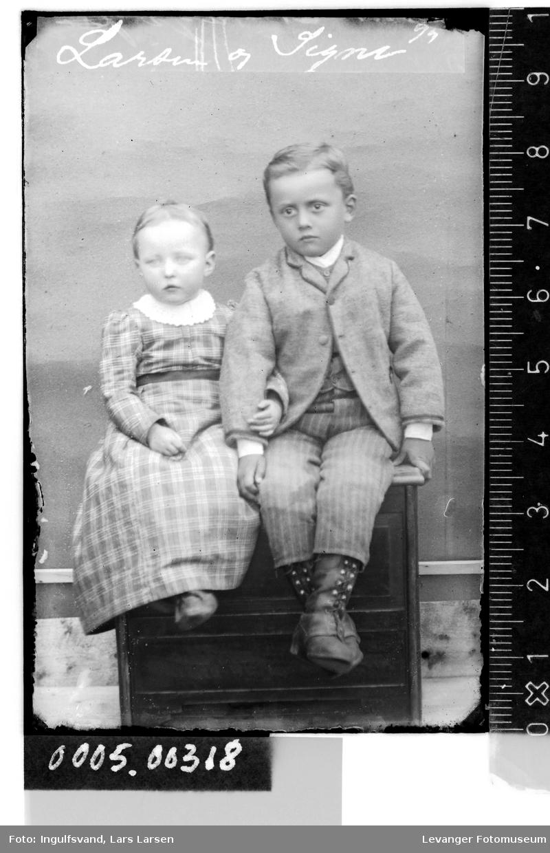 Portrett av jente og gutt i helfigur på en benk.