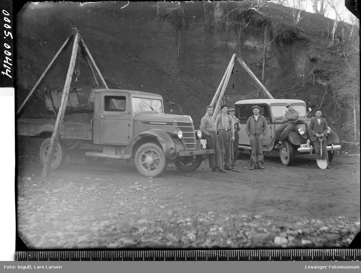 To lastebiler med stubbebrytere og arbeidskarer med spade i et grustak, forberedelse til vegarbeid.