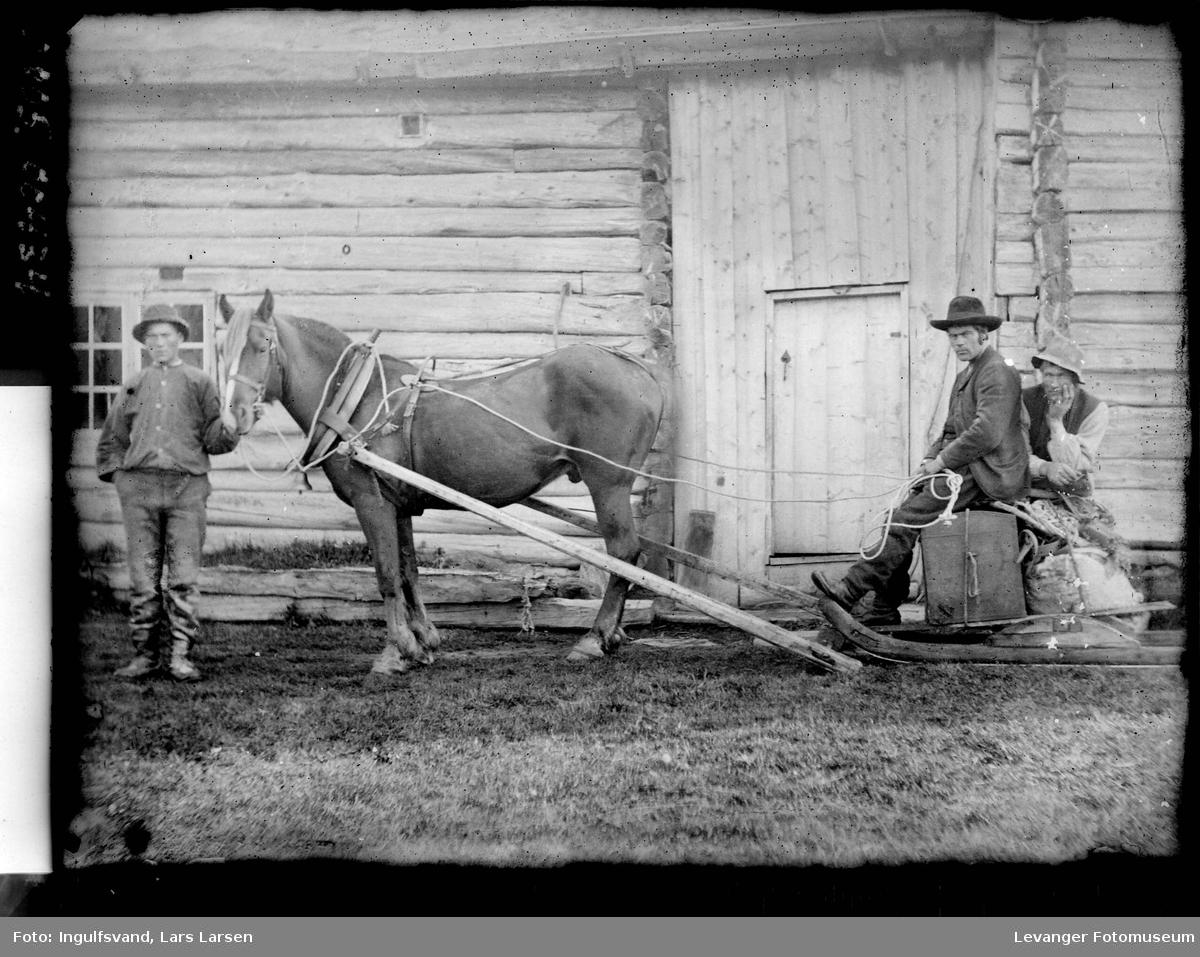 Hest på barmark med slede foran en lafta uthusbygning, to menn sitter på lasset  mens en annen mann holder hestens hodelag.