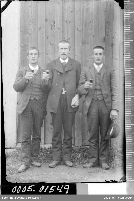 Portrett av tre menn som skåler.