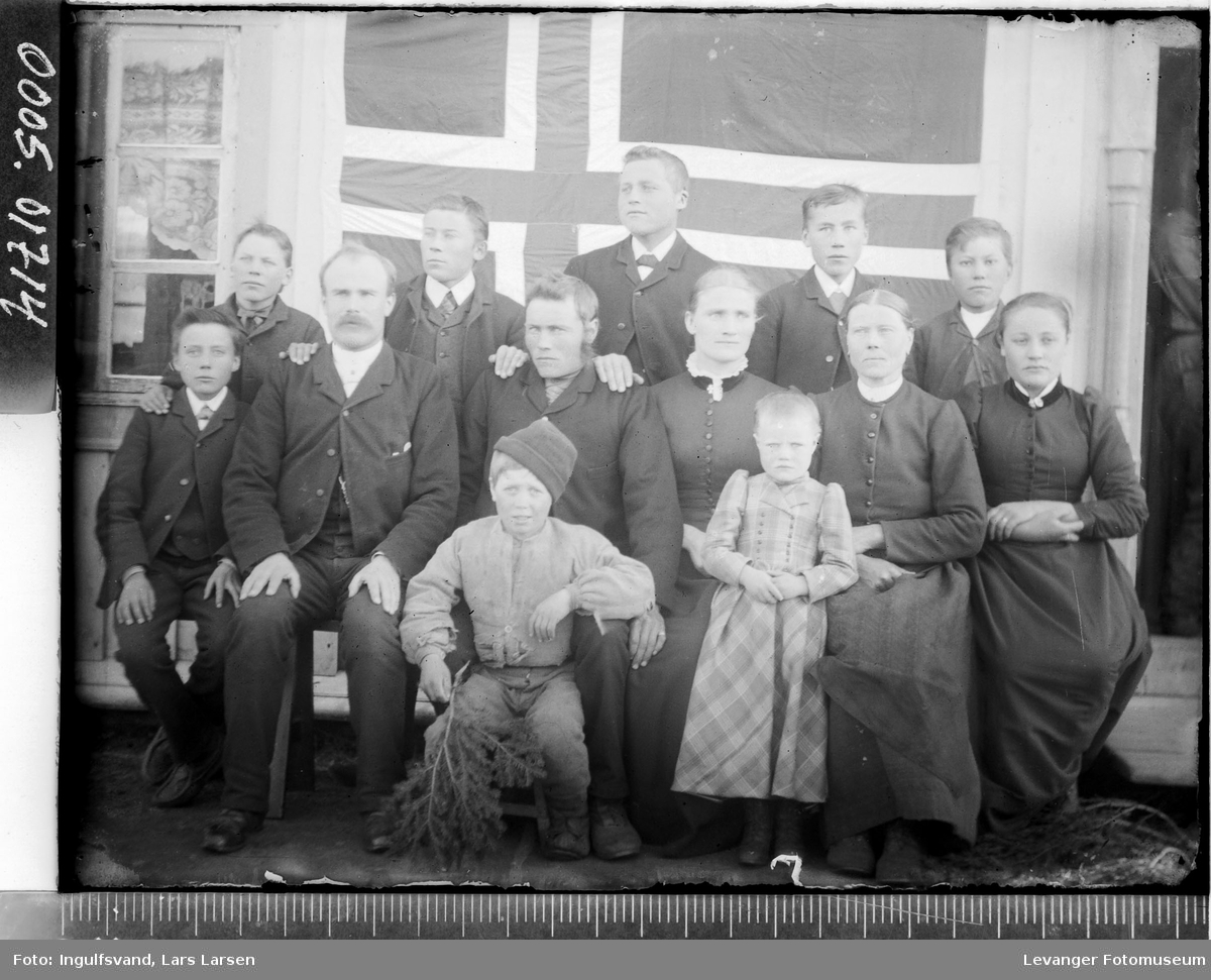 Gruppebilde av fem menn, tre kvinner og fem barn foran et flagg.