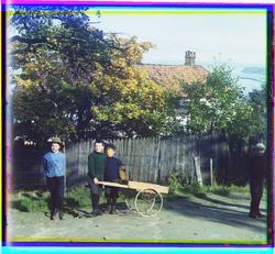 Fire gutter med håndkjerre foran en et hus med gjerde.