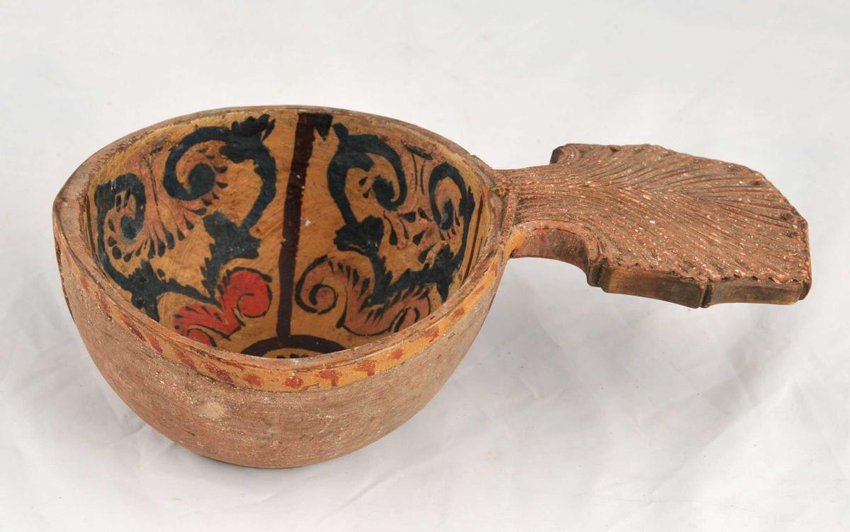 Uthola nute med handtak som er utskore, dekorera med måling. Initialar og årstal bak på handtaket, utskore eit kors under botn.